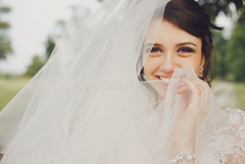 Bruds leendegnistrande, medan hon döljer den bak en skyla arkivfoton
