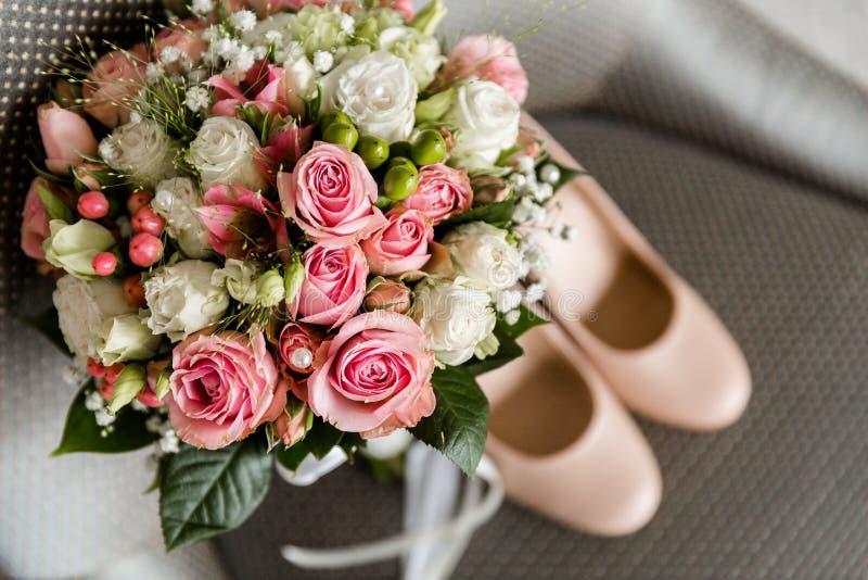 Bruds skor och bukett av blommor royaltyfria bilder