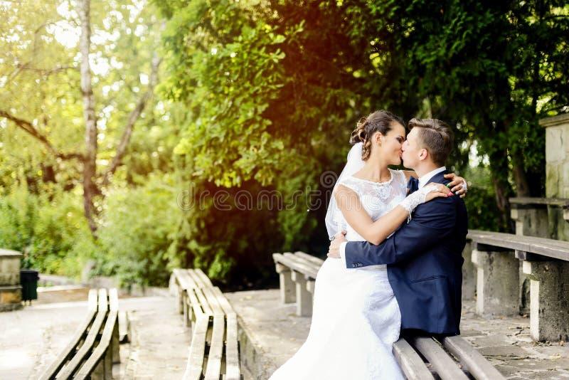 Brudsammanträde på brudgummens knä och kysser honom arkivfoton