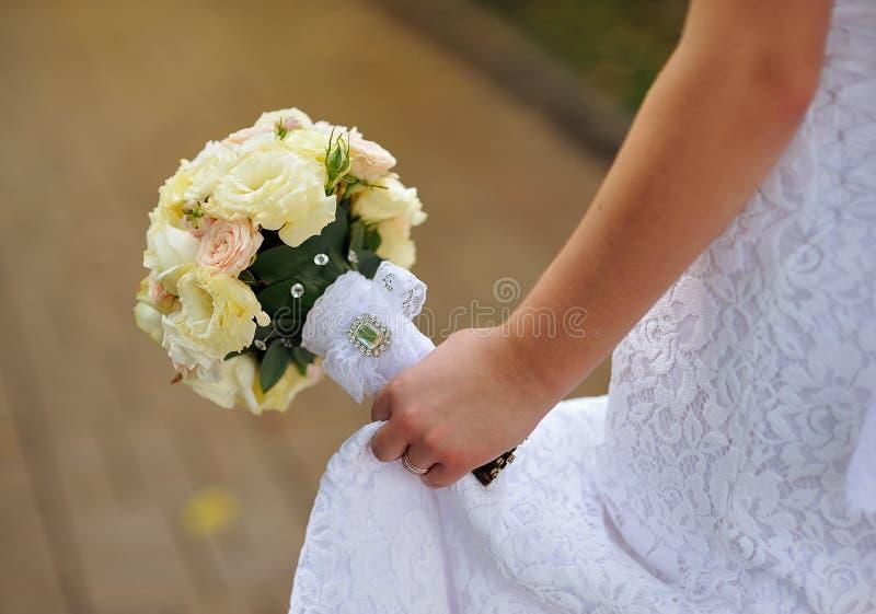 Brudsammanträde på hållande bröllopbukett för bänk av den olika blomman royaltyfri bild