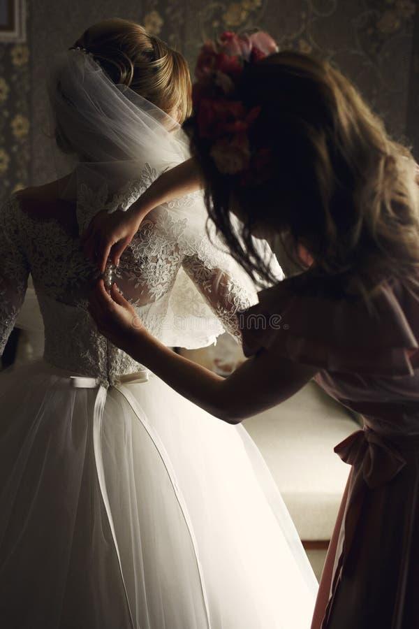 Brudtärna som förbereder den ursnygga blonda bruden i en elegant vit klänning royaltyfri foto
