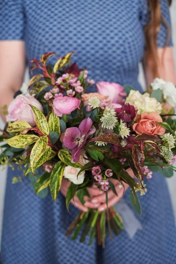 Brudtärna som rymmer den färgrika gifta sig buketten mot den blåa klänningen fotografering för bildbyråer