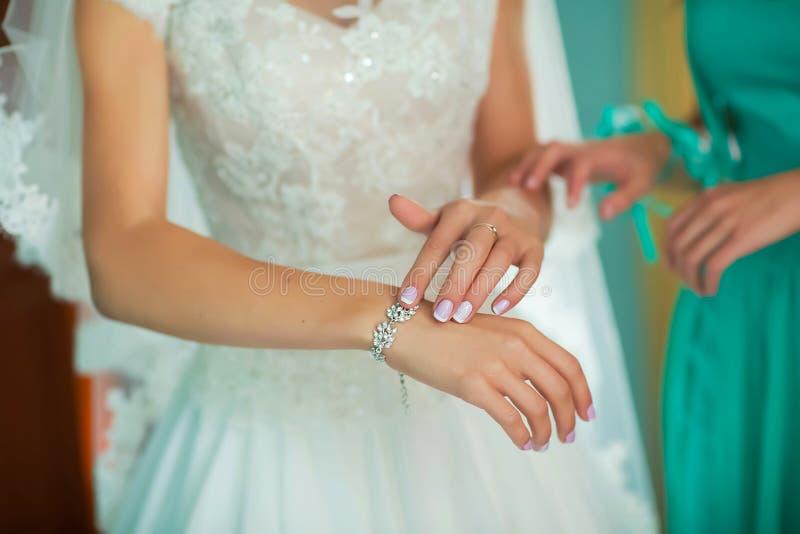 Brudtärnan som förbereder bruden för bröllopdagen, hjälp fäster upp en bröllopsklänning bruden för ceremonin, brud- klänningslut, royaltyfri foto