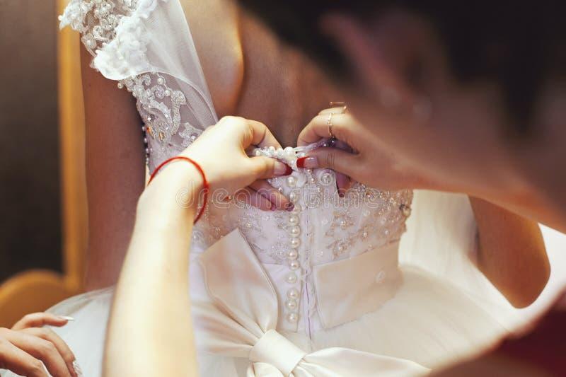 Brudtärnan som hjälper pålagt bröllop, snör åt klänningen räcker bakifrån c royaltyfri bild