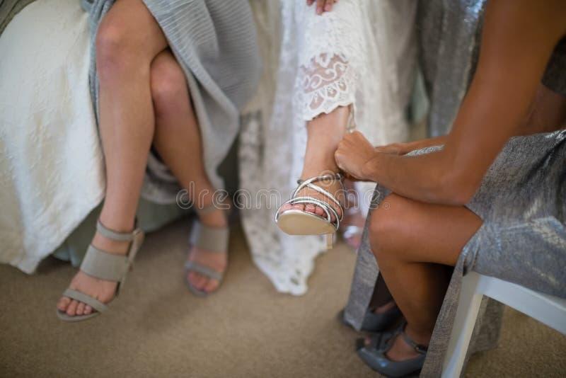 Brudtärnaportionbrud till pålagda bröllopskor arkivfoto