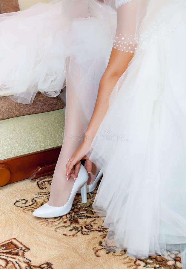 Brudtärnaportionbrud till pålagda eleganta skor royaltyfri foto