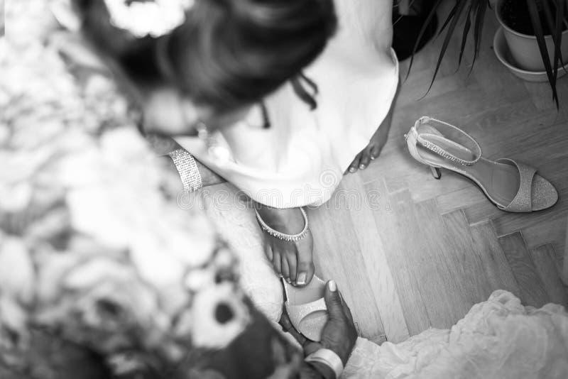 Brudtärnaportionbrud till pålagda vita skor royaltyfri foto