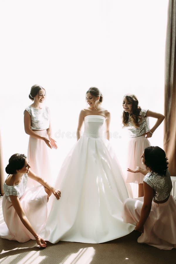 Brudtärnor hjälper med den brud- klänningen royaltyfria foton