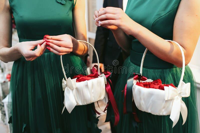 Brudtärnor i gröna klänningar rymmer korgar med röda kronblad arkivfoto