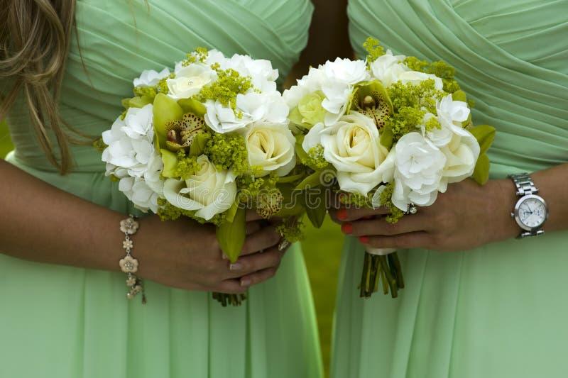 Brudtärnor i green med bröllopbuketten arkivbild