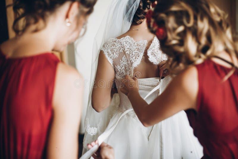 Brudtärnor i röda klänningar som hjälper den pålagda bröllopkappan för brud, mo arkivbilder