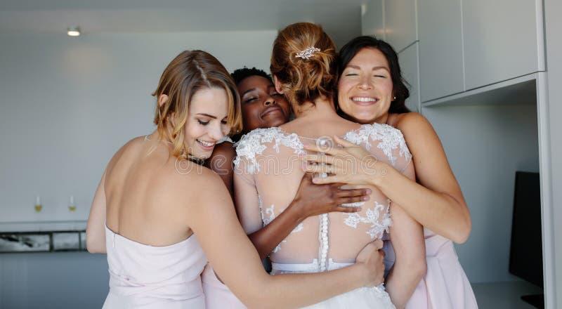 Brudtärnor som gratulerar bruden på bröllopdag royaltyfri fotografi