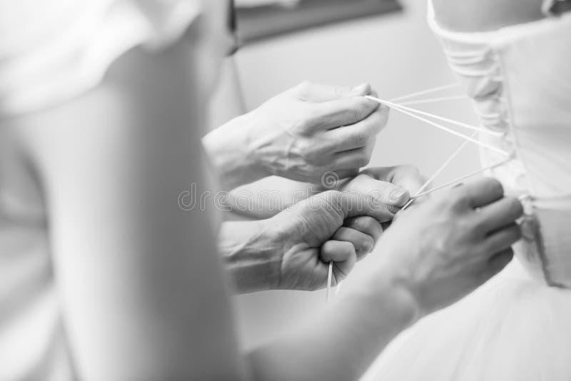 Brudtärnor som hjälper bruden att sätta på hennes klänning royaltyfria bilder