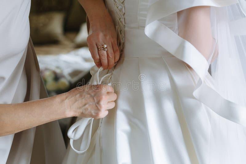 Brudtärnor som hjälper den pålagda bruden klänningen arkivbilder