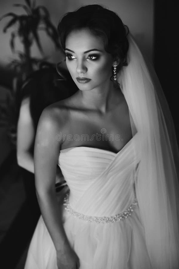 Brudtärnor som hjälper den ursnygga bruden, förbereder sig för att gifta sig closeup b royaltyfri foto