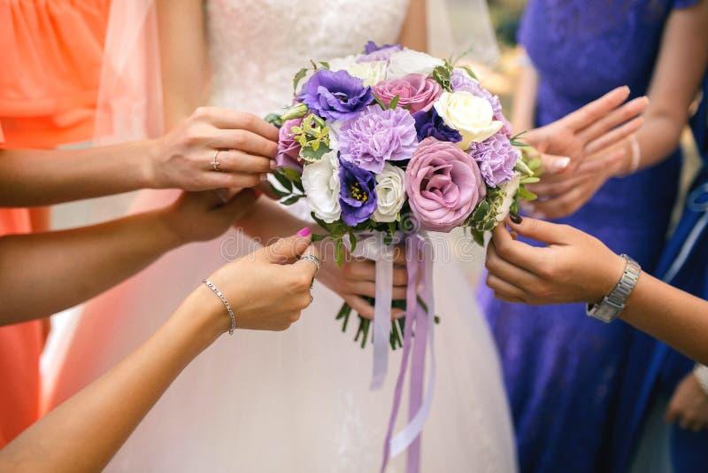 Brudtärnor som rymmer en bröllopbukett royaltyfri foto