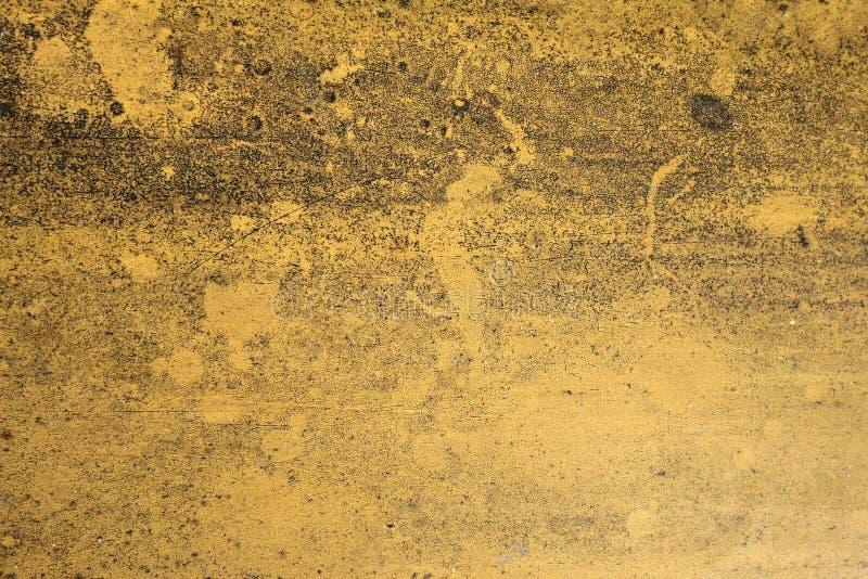 Brudzący wietrzał żółtego betonowej ściany tekstury tło zdjęcie royalty free