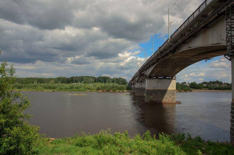 Brug aan de tegenovergestelde bank van de rivier, onder de bewolkte hemel in de lente royalty-vrije stock afbeelding