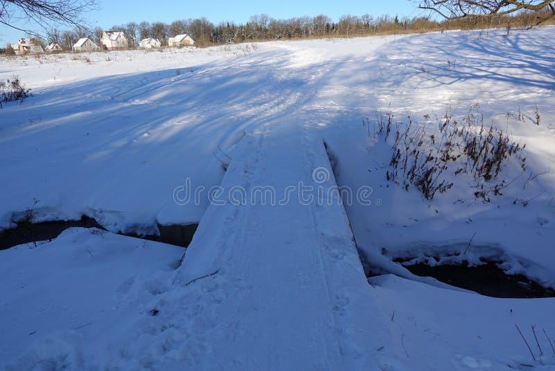 Brug en een beek, kreek van diepe sneeuw wordt omringd die stock foto