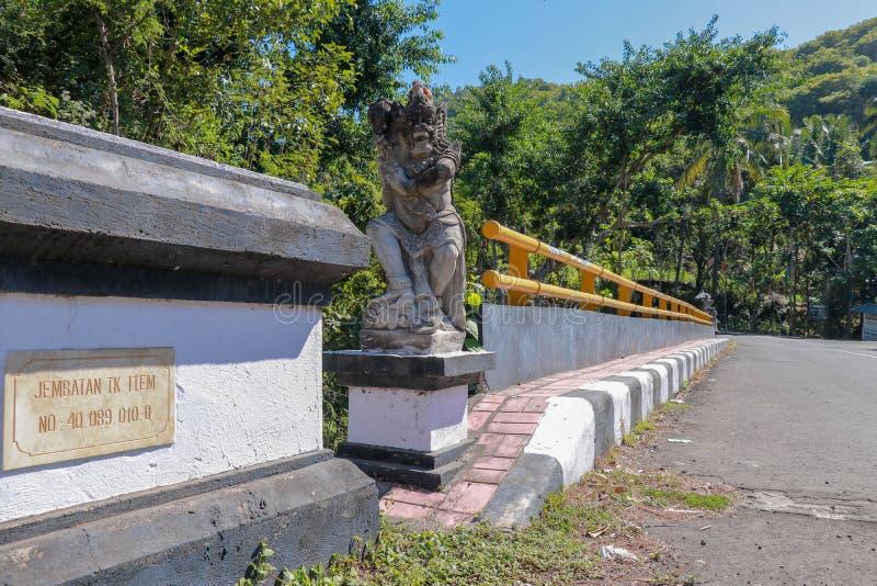 Brug met geel metaaltraliewerk over rivier in bergen op het eiland van Bali De decoratieve steenstandbeelden vertegenwoordigen my stock afbeeldingen