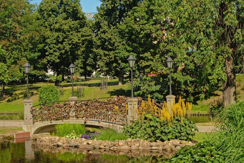 Brug met lantaarns en veel liefdesloten op ballustrade in het park van de het Bastionheuvel van Riga royalty-vrije stock afbeeldingen