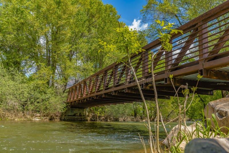 Brug met metaalvangrails over het glinsterende water in Ogden River Parkway stock foto's
