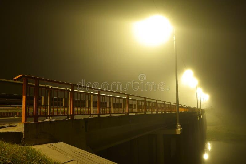 Brug over de rivier en het omhulde licht van straatlantaarns in zware mist bij nacht royalty-vrije stock foto