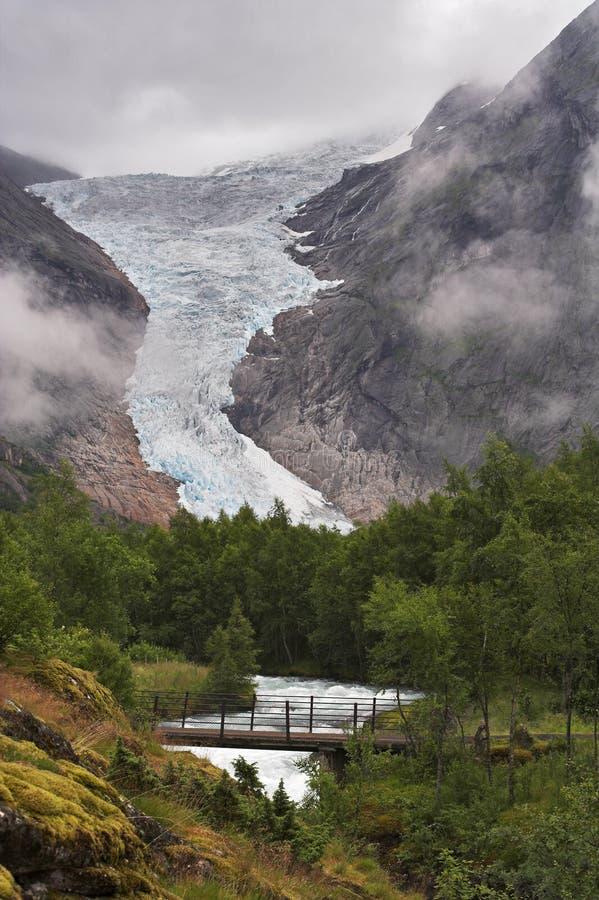 Brug over de stroom bij gletsjer Briksdal stock foto's