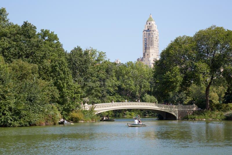 Brug van de Central Park de witte Boog met mensen en boten in New York stock afbeelding