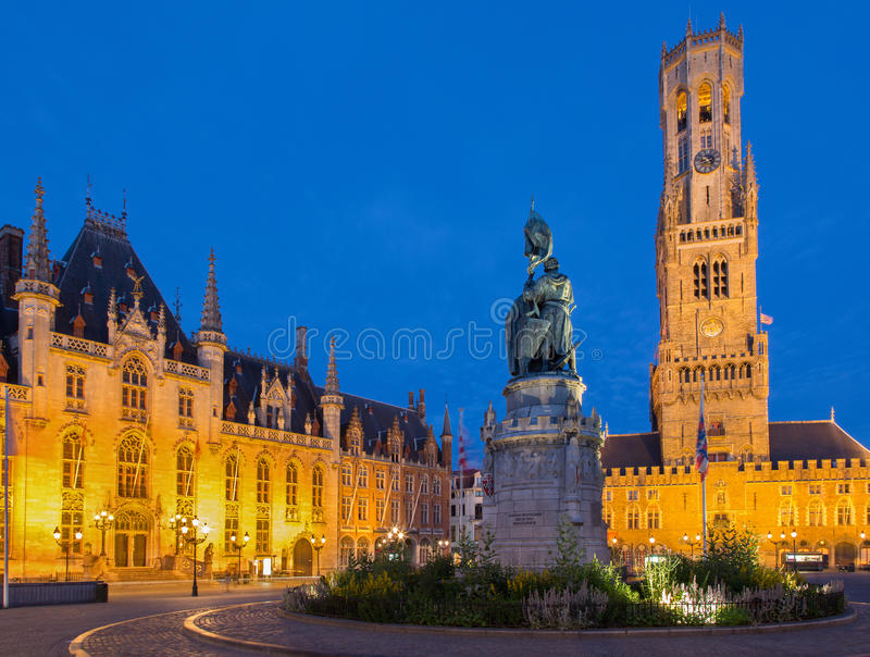 Bruge - Grote markt in evening dusk. Belfort van Brugge and Provinciaal Hof buildings. And and memorial of Jan Breydel and Pieter De Coninck stock photo