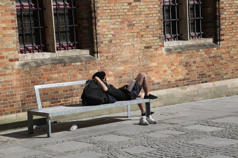 BRUGES, BELGIA -03 27 2017 czyta książkę na ławce z jego butami brać młody człowiek fotografia stock