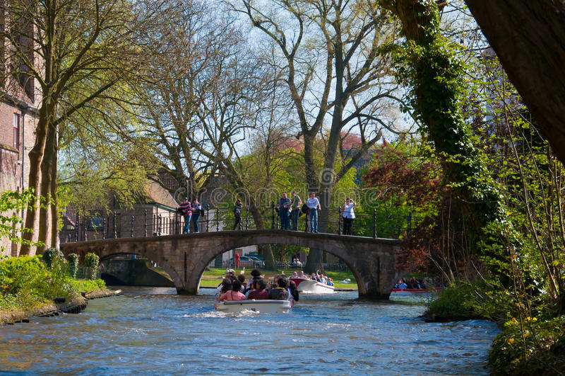 Bruges Belgien - April 10: Oidentifierade turister besöker den medeltida staden av brugge genom att använda de typiska fartygen öv arkivfoton