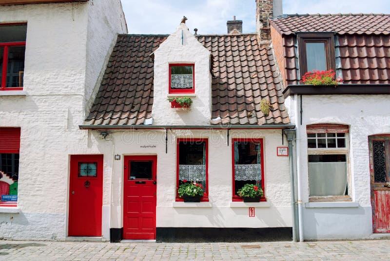 Bruges Belgien - Augusti 2010: Små pittoreska vita hus med röda dörrar, röda fönsterramar, röda blommor och röda taktegelplattor arkivbilder
