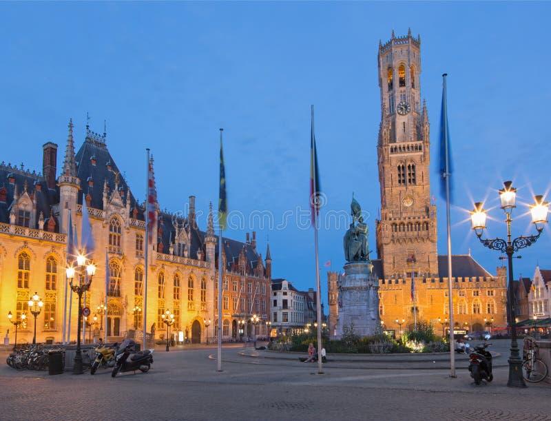 BRUGES BELGIEN - JUNI 13, 2014: Grote markt i aftonskymning Belfort skåpbil Brugge och Provinciaal Hof byggnader royaltyfri bild
