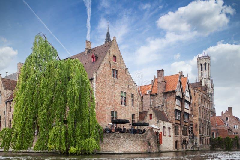 Bruges Belgien - Maj 17, 2012: Det ber?mda klockstapeltornet, de gamla husen och ett gatakaf? p? vattenkanalen i Bruges p? arkivbild