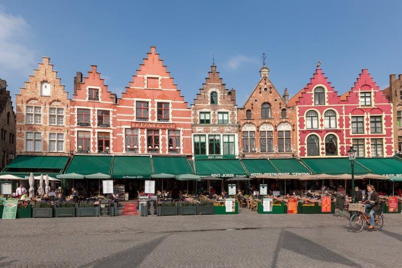 BRUGES BELGIEN - MARS 23, 2015 Turister i norrsida av Grote Markt (marknadsfyrkant) av Bruges, Brugge, med den förtrollande gatan royaltyfri bild