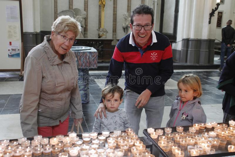 Family: grandmother, father and two little girls sisters light candles inside the church royalty free stock photo