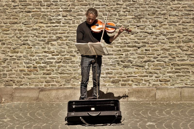 BRUGES, BELGIUM - JUNE 10, 2017: The street musician at an ancient stone wall. The man the musician plays a violin on the street of Bruges royalty free stock photography