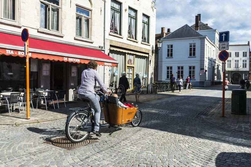 Street with people walking and cycling in Bruges, Belgium. Bruges, Belgium - September 1, 2017: Street with people walking and a woman cycling with a Babboe stock image