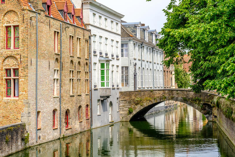 Bruges & x28; Brugge& x29; pejzaż miejski z wodnym kanałem i mostem fotografia royalty free