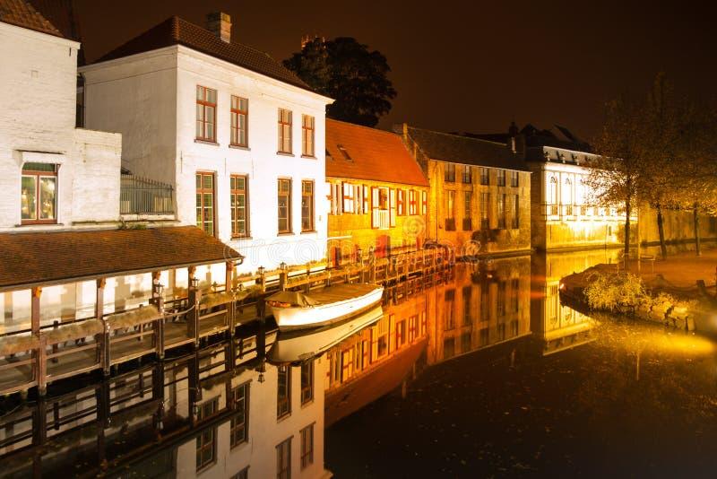 Bruges di notte Canale calmo di Dijver con la barca nel bacino belgium fotografie stock libere da diritti