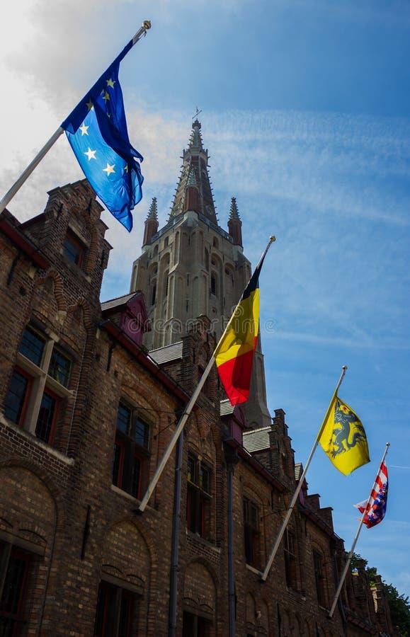 Bruges flaggor och kyrkatorn royaltyfri bild