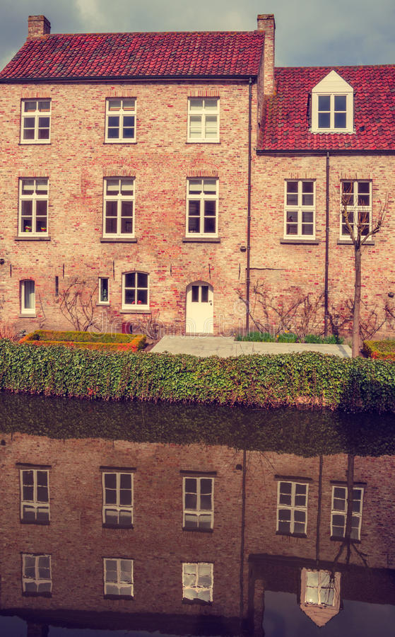 Bruges - hus reflekterade på kanalen royaltyfri bild