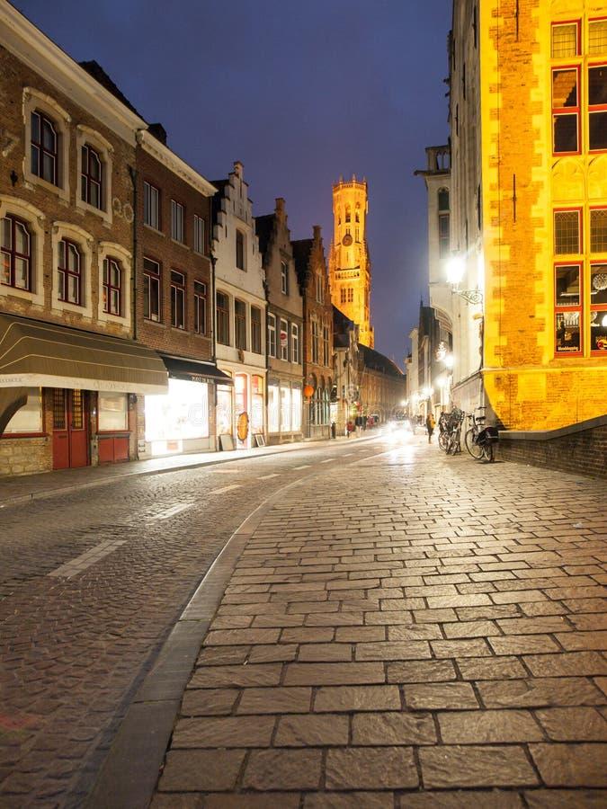 Bruges na noite Rua Cobbled e centro de cidade histórico iluminado com torre de Belfort, Bélgica, Europa imagem de stock royalty free