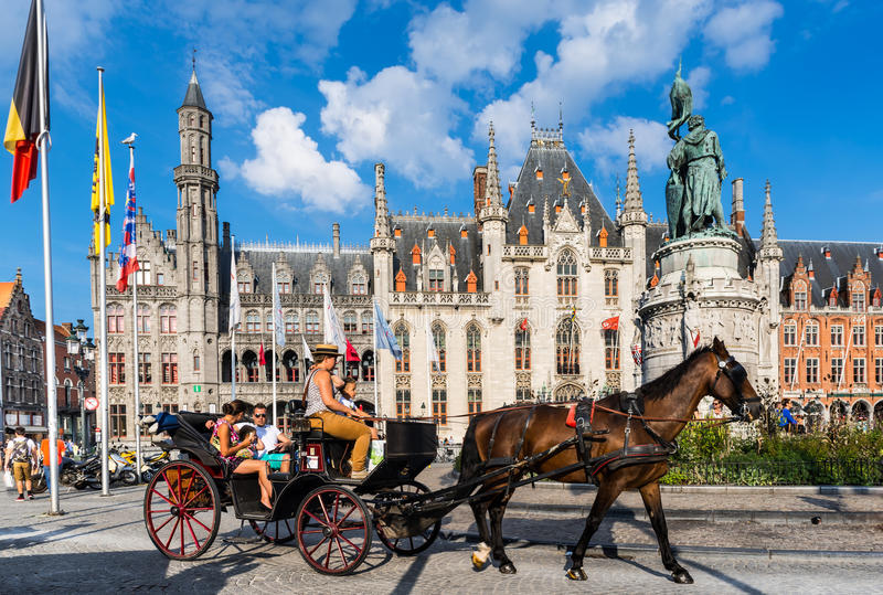 Bruges, Provinciaal Hof, Belgium. BRUGES, BELGIUM - 7 AUGUST 2014. Horse-drawn carriage with tourists in front of Provinciaal Hof, Brugge, Flanders government royalty free stock image