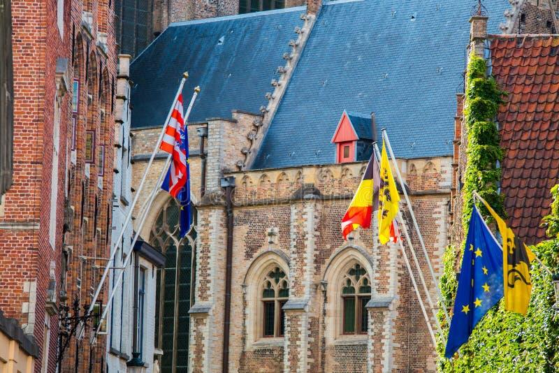 Bruges sight EU-, Belgien och Bruges flaggor på historisk byggnadbakgrund royaltyfri bild