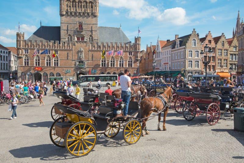 BRUGGE, BELGIË - JUNI 13, 2014: Het Vervoer op Grote Markt en de bestelwagen Brugge van Belfort op achtergrond stock afbeelding