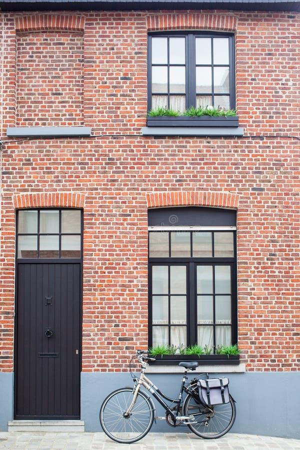 Brugge, Belgi? - Augustus 16, 2013: Weergeven van de muur met vensters, donkere deur en uitstekende fiets met zak stock afbeeldingen