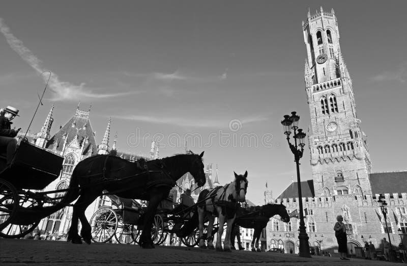 BRUGGE BELGIEN - JUNI 13, 2014: Vagnen på den Grote Markt och Belfort skåpbilen Brugge royaltyfri foto