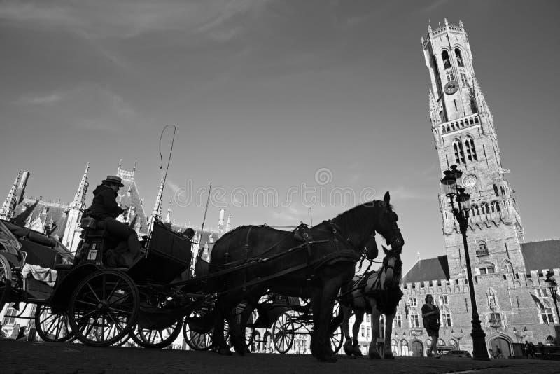 BRUGGE BELGIEN - JUNI 13, 2014: Vagnen på den Grote Markt och Belfort skåpbilen Brugge arkivfoton